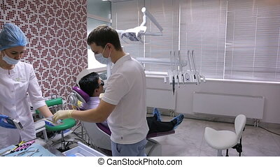 Doctors prepare for teeth treatment in working cabinet....