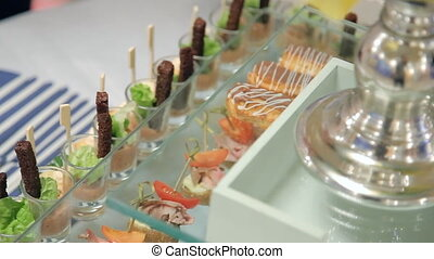 Close-up view of waiter putting eclairs on glass stand on table.