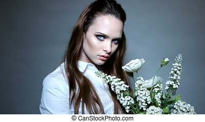 Beautiful portrait of a young woman holding white flowers...