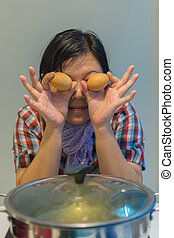 Asia woman cooking by put a flesh egg in to a hot pot - Asia...