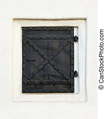 Old black metal door, closed, in white wall