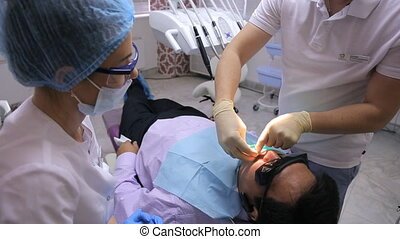 Dentist and his assistant stand near patient in working...