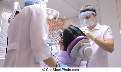 Doctor with his assistant are busy with treatment of teeth...