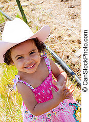 Little Cowgirl - A young girl wears a pink dress, a cowboy...