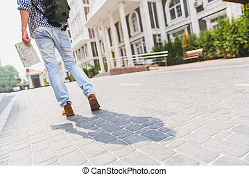 Touristic young man walking in city - Low angle of male...