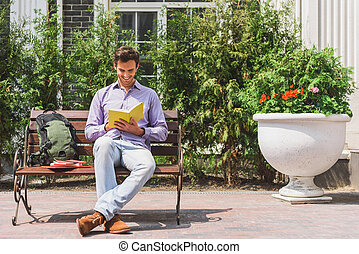Clever young man studying outdoors