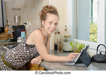 smiling young woman using a tablet computer - a smiling...