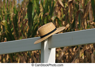 Amish straw hat laying over fence post with corn field in...