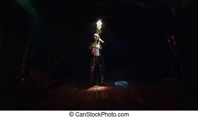 Scrubwoman sing on stage in concert microphone in closed bar. Energy dance.