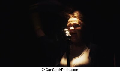 Scrubwoman with mop start sing into microphone on stage of...