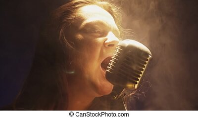 Scrubwoman sing in vintage microphone on stage of club. Dance under spotlight
