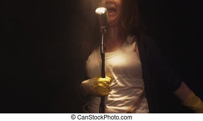 Scrubwoman sing in vintage microphone on stage of club. Dance. Smoke. Run away