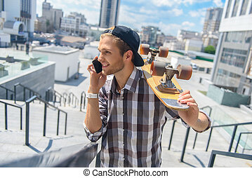 Cheerful male skater communicating on phone - Happy young...