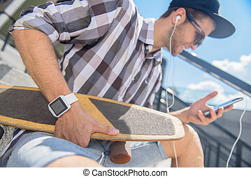Joyful male skater entertaining with phone - Happy young man...