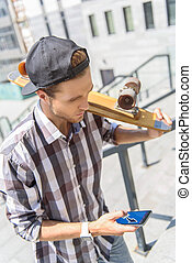 Pensive male skater messaging on phone - Serious young man...