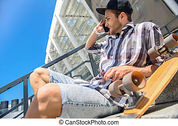 Cheerful male skater entertaining with telephone - Carefree...