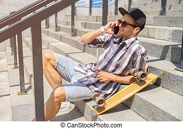 Happy young man with skate using smartphone - Cheerful male...