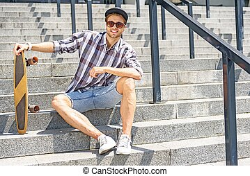Carefree male skater sitting on stairs - Joyful young guy is...