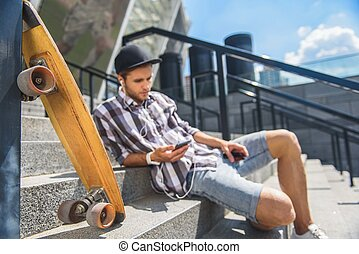 Thoughtful male skater listening to music form earphones -...