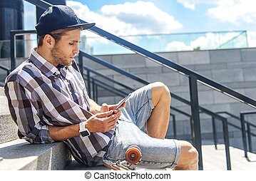 Skillful male skater using smartphone - Cool young man is...