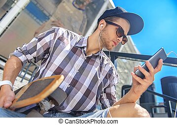 Cheerful young guy resting with skate and phone - Thoughtful...