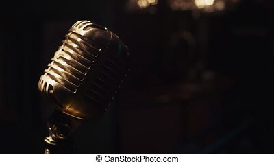 Concert metal microphone on stage under spotlight. Scrubwoman full on bar stand.