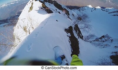 Snowboarder backcountry ride from top of snowy mountain....