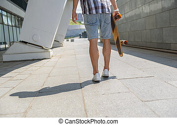 Cheerful male skateboarder having walk outdoors - Close up...