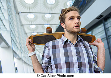 Pensive guy resting with skateboard - Confident young man is...