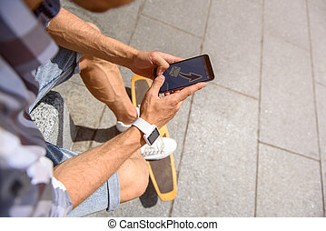 Young man with skateboard using phone - Top view of young...