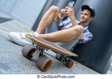 Happy male skater entertaining with smartphone - Cheerful...