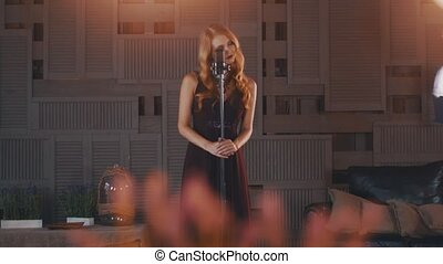 Attractive jazz vocalist in black dress perform on stage at microphone. Dancing