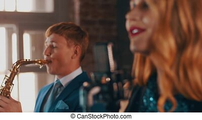 Attractive jazz vocalist performing on stage with saxophonist in blue suit. Live