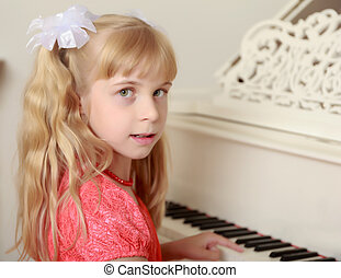 Girl sitting at the piano - Beautiful little girl in a long...