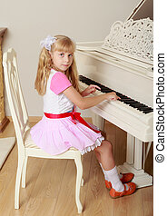 Girl playing the piano - Cute little blonde girl plays the...