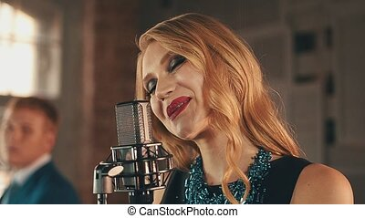 Singer with red lips perform on stage at microphone. Retro...