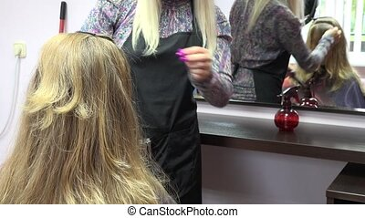 stylist brush woman washed hair and cut hair ends to mirror....
