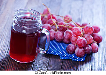 grape juice in glass and on a table