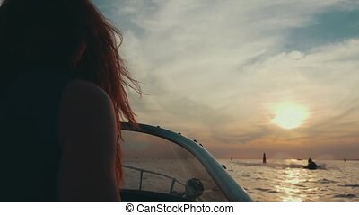 Red hair girl drive motor boat to summer sunset. Romantic evening. Nature.