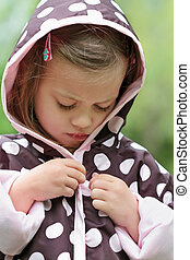 Child Putting on Raincoat - Little girl dresses herself in a...