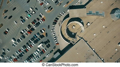 Aerial overlooking the parking with cars and people. Shoot...