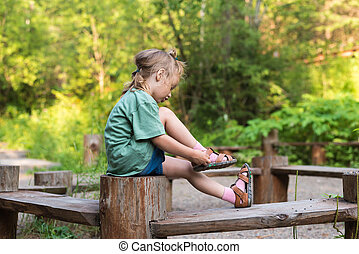 Little girl putting her sandal on. She is sitting on a...
