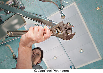 Woman tightens nut aerator tap, using monkey wrench. -...