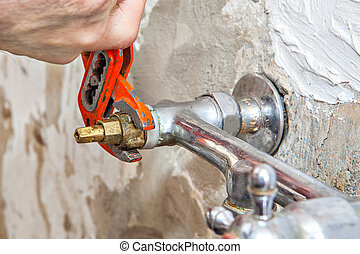 Plumber fixing water tap valve in kitchen, users pliers...