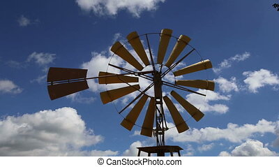 Old ranch windmill on a sky background time lapse