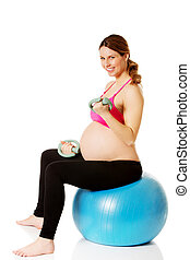 Young pregnant woman doing exercise at home