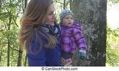 newborn baby in arms of mother nature in autumn on...