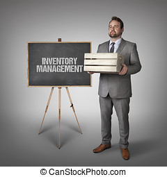 Inventory management text on blackboard with businessman...