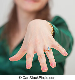 Woman shows new ring with blue gem - A woman shows off her...