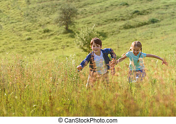 Boy and girl running on field - Waiting for us, parents...